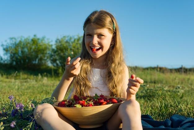 Garota atraente criança comendo morango Foto Premium