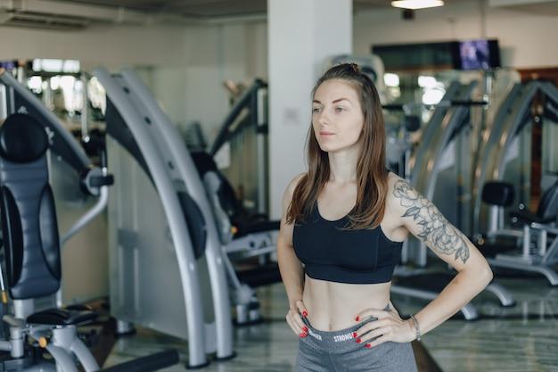 Garota atraente e atlética fica na parede de simuladores no ginásio. estilo de vida saudável. Foto gratuita