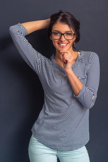Garota atraente em óculos está segurando um grampo de cabelo nos dentes. Foto Premium