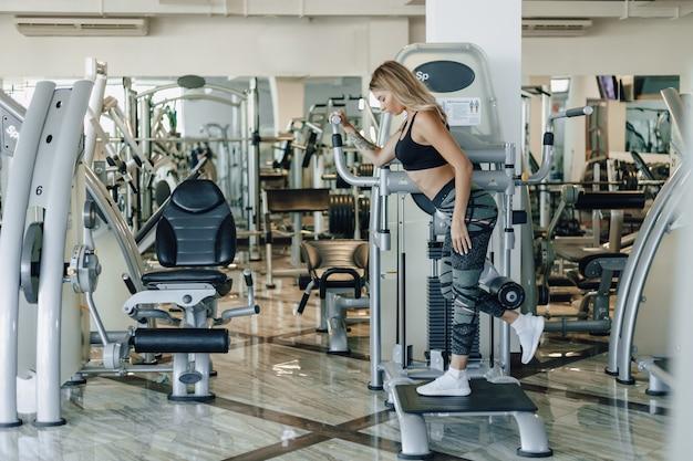 Garota atraente esportes realiza exercícios nos quadris e nádegas. estilo de vida saudável. Foto gratuita