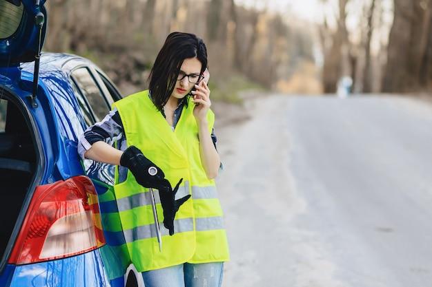 Garota atraente, falando por telefone perto de carro na estrada em jaqueta de segurança Foto Premium
