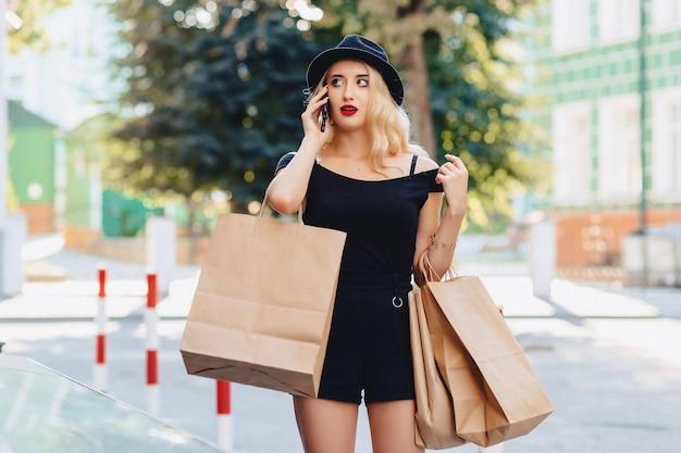 Garota atraente loira em um chapéu depois de fazer compras nos raios do sol de verão com telefone Foto Premium