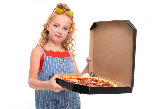 Garota atraente mantém uma caixa aberta com pizza em um branco Foto Premium