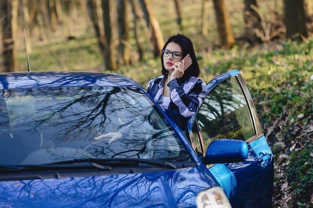 Garota atraente motorista parece fora da porta aberta do carro e falando no telefone Foto Premium