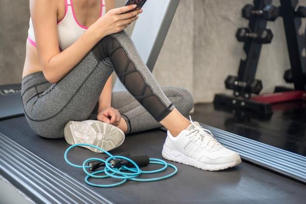 Garota atraente no ginásio com um telefone Foto Premium
