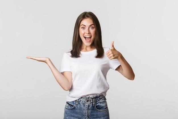 Garota atraente satisfeita segurando algo por lado e mostrando o polegar para cima em aprovação. Foto gratuita