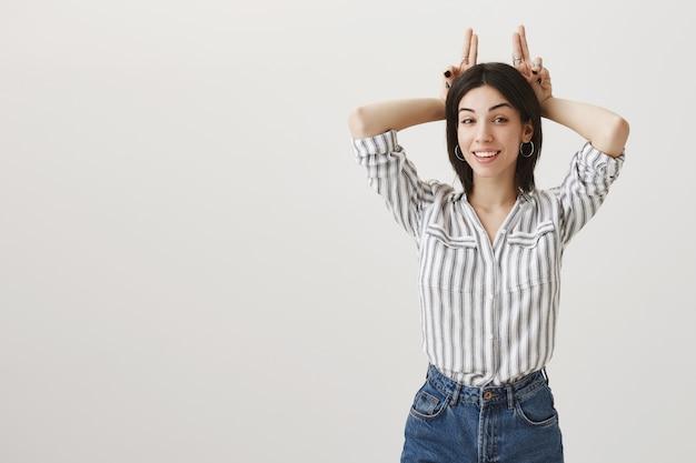 Garota atraente sorridente mostrando gesto de chifres, sendo teimosa Foto gratuita
