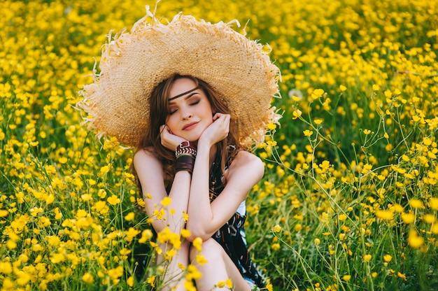Garota bonita em um campo de flores amarelas Foto Premium