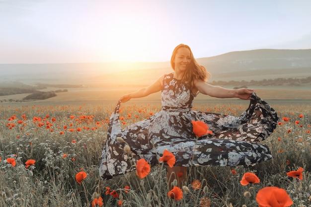 Garota bonita em um campo de papoulas ao pôr do sol. conceito de liberdade Foto Premium