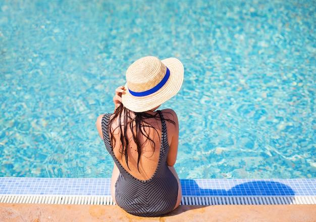 Garota bonita em um maiô preto perto de uma piscina azul. Foto Premium