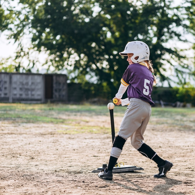 Garota bonita em um uniforme de beisebol, em um capacete, joga beisebol, em torno de seu treinador diz como saltar a bola Foto Premium