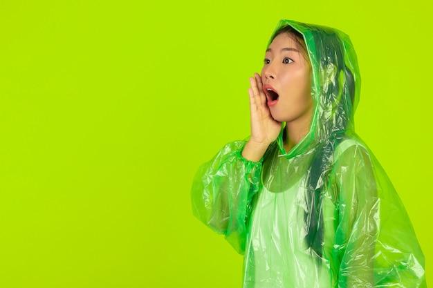 Garota bonita feliz, vestindo roupas verdes, guarda-chuva e casaco, dia chuvoso. Foto gratuita
