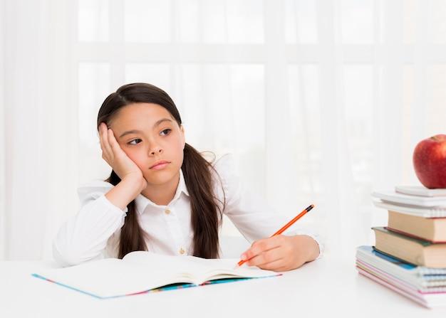 Garota cansada, pensando e fazendo lição de casa Foto gratuita