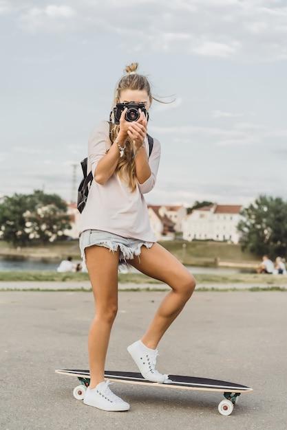 Garota com cabelo comprido com skate fotografando na câmera. rua, esportes ativos Foto gratuita