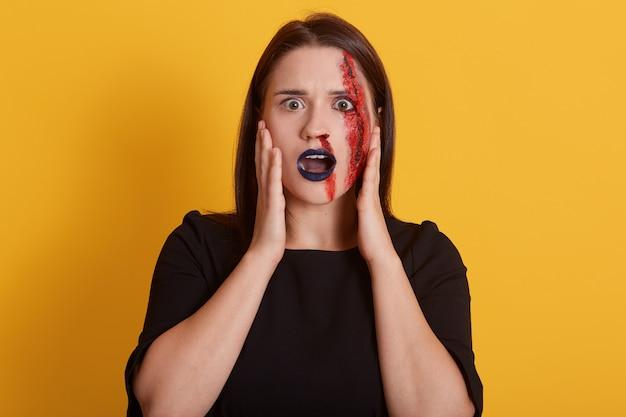 Garota com cabelo liso e escuro, com ferida sangrenta no rosto, olhos grandes e cheios de medo, mantém a boca ligeiramente aberta, vê vampiro, assassino ou psicopata na frente dela, conceito de halloween. Foto gratuita