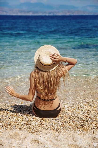 Garota com cabelo loiro encaracolado em biquíni preto relaxante na praia Foto Premium