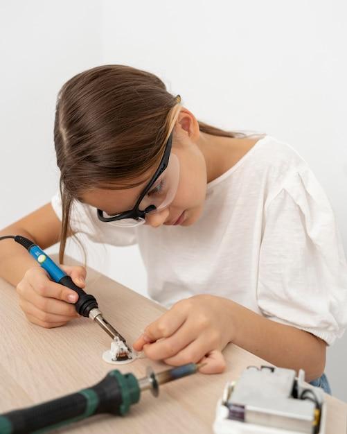 Garota com óculos de proteção fazendo experimentos científicos Foto gratuita