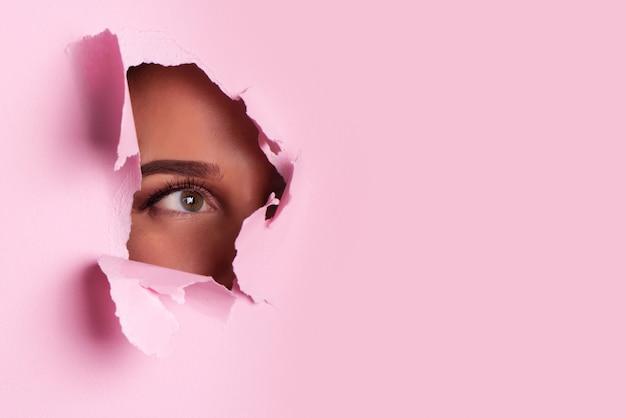 Garota com olhos brilhantes compõem parece através do buraco de papel rosa Foto Premium