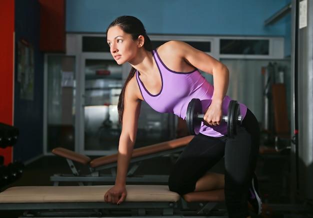 Garota com pilotos na academia fazendo exercícios musculares Foto gratuita