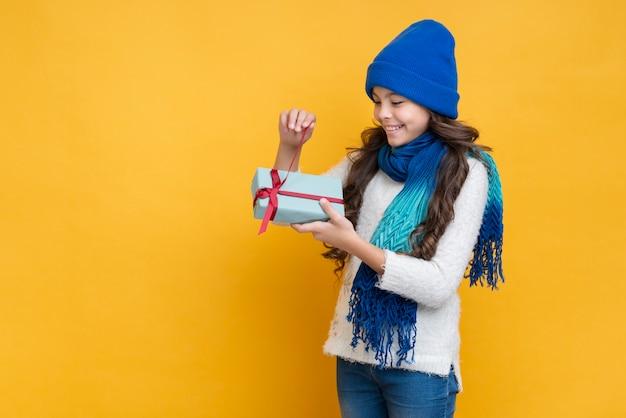 Garota com roupas de inverno, desembalar um presente Foto gratuita
