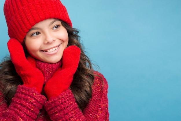 Garota com roupas de inverno vermelho, olhando para a esquerda Foto gratuita