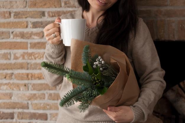Garota com um buquê de galhos nas mãos, em papel pardo. perto da parede de tijolos. com uma caneca de café nas mãos Foto Premium