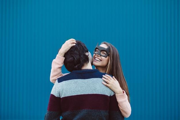 Garota com uma máscara beijando seu jovem. Foto gratuita