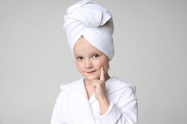 Garota com uma túnica branca e uma toalha na cabeça depois de um banho e lavar o cabelo. cosméticos para crianças e cuidados com a pele, tratamentos de spa. cabelo limpo e bonito. Foto Premium