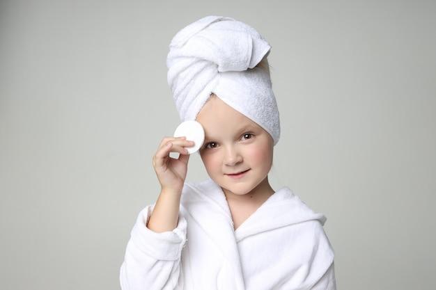 Garota com uma túnica branca e uma toalha na cabeça depois de um banho e lavar o cabelo. cosméticos para crianças e cuidados com a pele, tratamentos de spa. Foto Premium