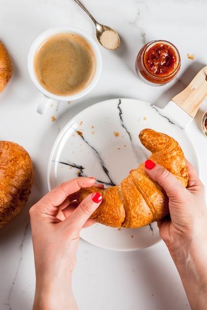 Garota come café da manhã continental caseiro, croissants, café. geléia Foto Premium