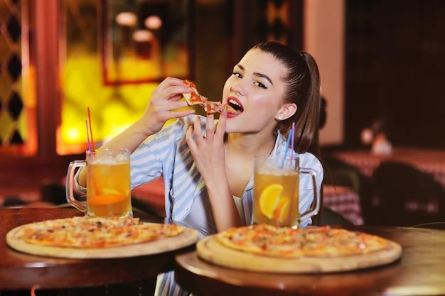 Garota comendo pizza e bebendo cerveja ou um coquetel de citrinos de cerveja no fundo de um bar ou pizzaria. Foto Premium