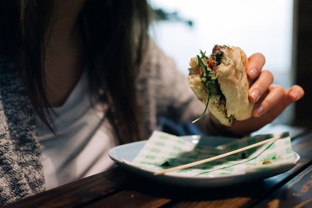 Garota comendo sanduíche de bife argentino Foto gratuita