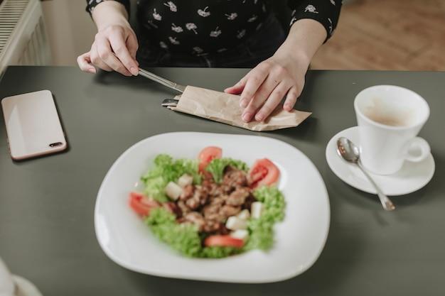 Garota comendo uma salada em um restaurante Foto gratuita