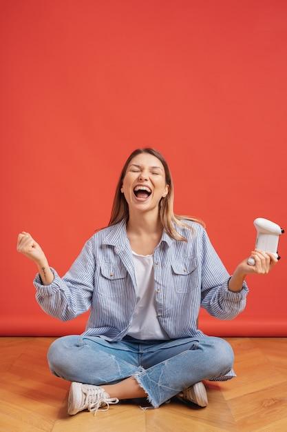 Garota competitiva comemora vencedor segurando o controlador de joystick de jogo na parede vermelha. Foto gratuita