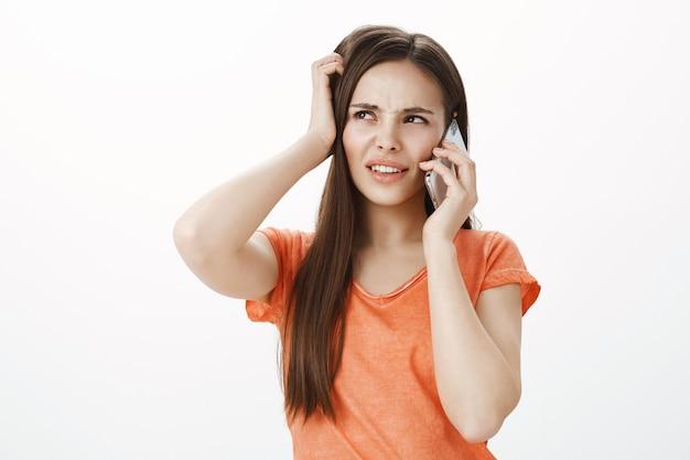 Garota confusa e insegura, parecendo intrigada no canto superior esquerdo enquanto fala no celular Foto gratuita