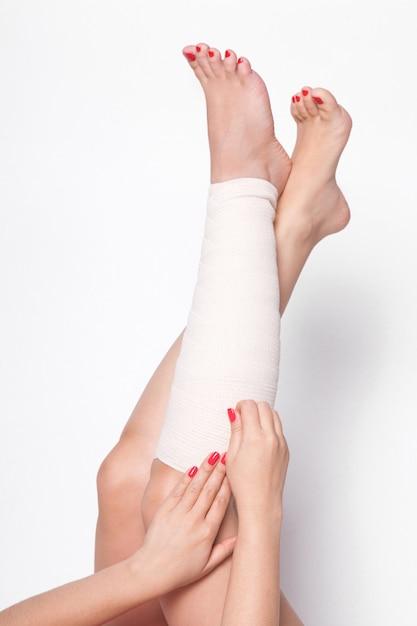 Garota corrige um curativo elástico nas pernas Foto Premium