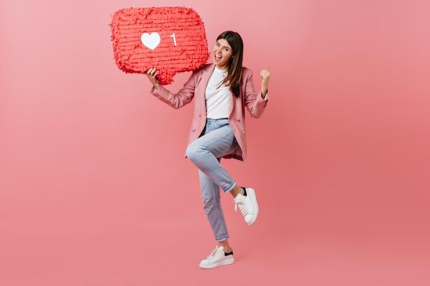Garota curtindo o feedback da rede social. foto de estúdio de jovem dançando com o ícone semelhante no fundo rosa. Foto gratuita