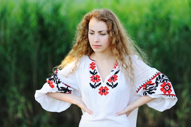 Garota da camisa nacional ucraniana em fundo de grama Foto Premium