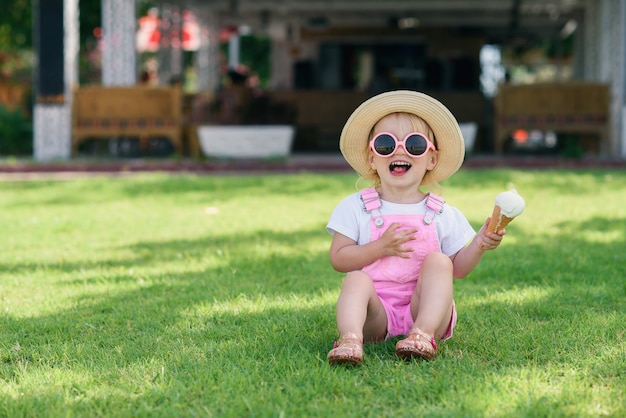 Garota da criança em macacões de verão rosa, chapéu e óculos de sol rosa senta-se em uma grama verde com sorvete na mão e sorrindo. Foto Premium
