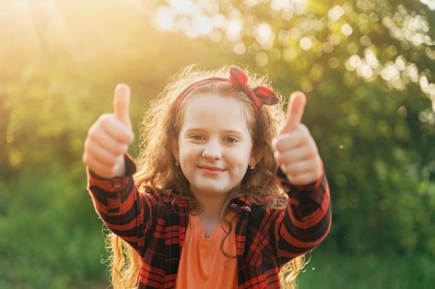 Garota da risada mostrando os polegares. Foto Premium