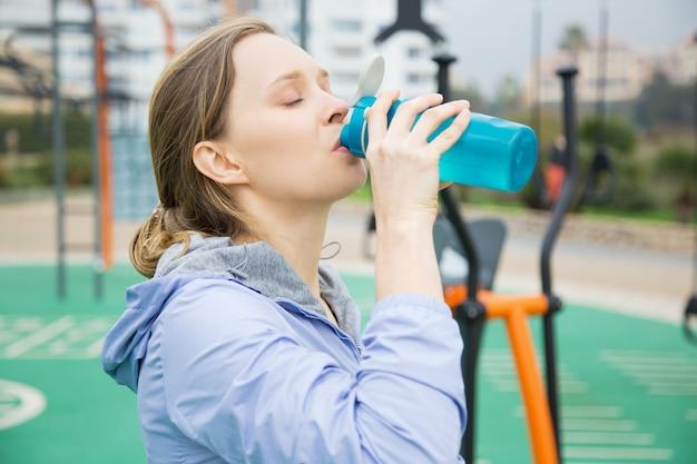 Garota de ajuste cansado com sede durante exercícios físicos Foto gratuita