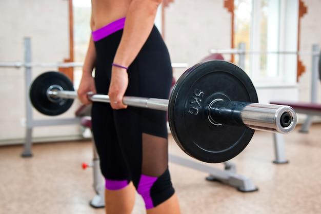 Garota de aptidão muscular fazendo exercício pesado deadlift no ginásio Foto Premium