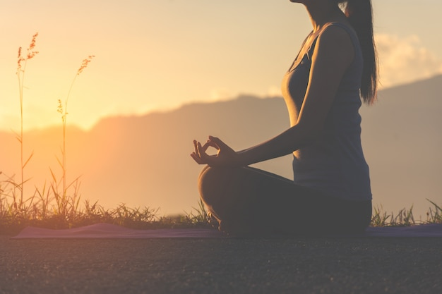 Garota de aptidão silhueta praticando ioga na montanha com luz do sol Foto Premium