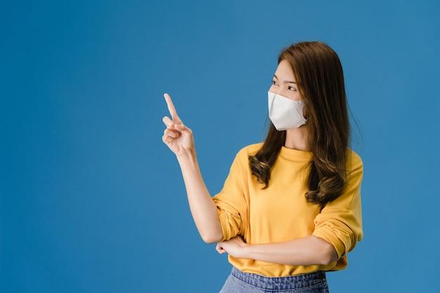 Garota de ásia jovem usando máscara médica mostra algo no espaço em branco com vestido de pano casual e olhando para a câmera isolada sobre fundo azul. distanciamento social, quarentena para o vírus corona. Foto gratuita