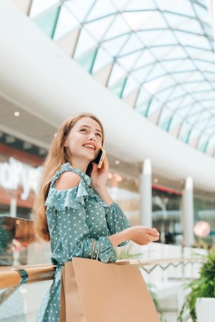 Garota de baixo ângulo com sacos de compras no shopping Foto gratuita