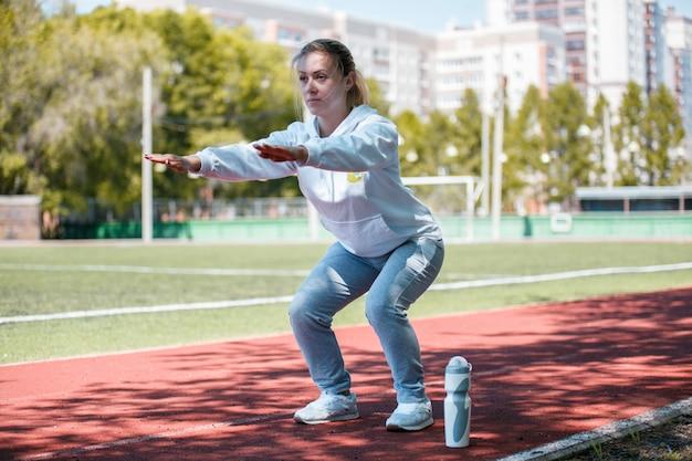 Garota de beleza squatting.young fazer exercícios no estádio Foto Premium
