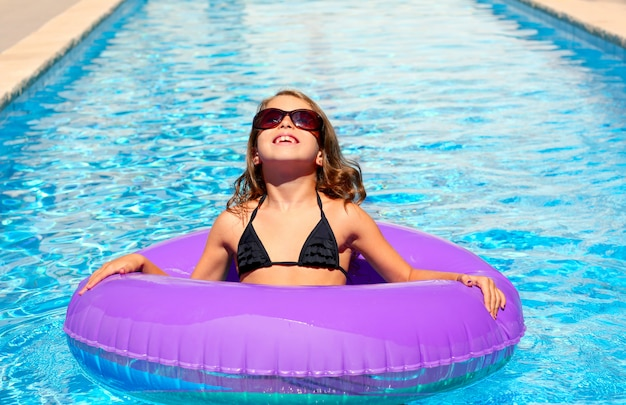 Garota de biquíni com óculos de sol e anel de piscina inflável Foto Premium