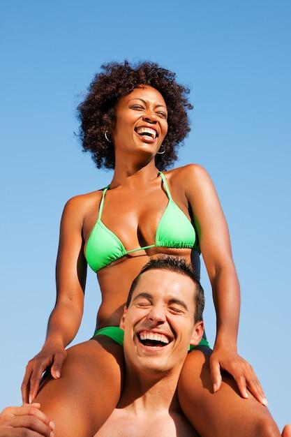 Garota de biquíni verão sentado nos ombros do homem Foto Premium