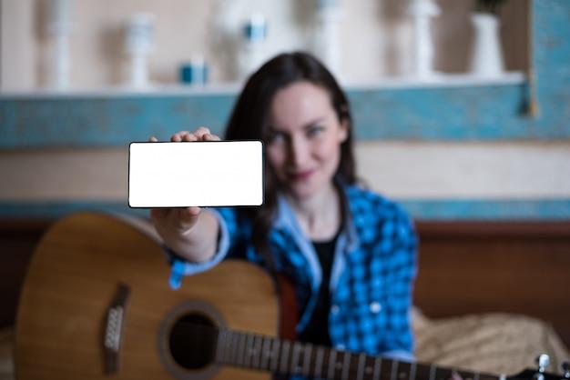 Garota de camisa azul e calça jeans com violão mostra a mão com o smartphone. Foto Premium
