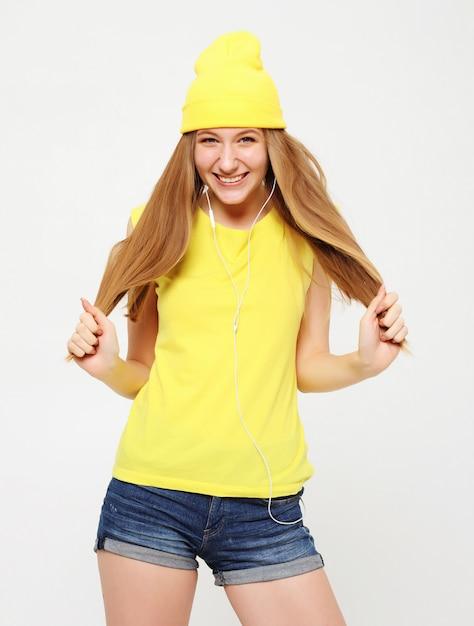Garota de camiseta amarela dançando com a expressão do rosto inspirado. Foto Premium